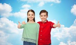 Den lyckliga pojke- och flickavisningen tummar upp Arkivfoto