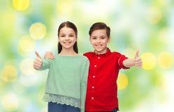 Den lyckliga pojke- och flickavisningen tummar upp Fotografering för Bildbyråer