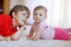 Den lyckliga pojken för den lilla ungen med nyfött behandla som ett barn flickan, gullig syster syskon Brodern och behandla som e Royaltyfria Foton