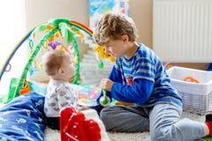 Den lyckliga pojken för den lilla ungen med nyfött behandla som ett barn flickan, gullig syster syskon Brodern och behandla som e Royaltyfri Bild