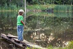 Den lyckliga pojken går att fiska på floden, en barnfiskare med a royaltyfri bild