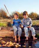 Den lyckliga pojken går att fiska på floden med husdjuret, barn ett och satsen Royaltyfri Foto