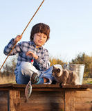 Den lyckliga pojken går att fiska på floden med husdjuret, barn ett och satsen Arkivbild