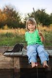 Den lyckliga pojken går att fiska på floden med husdjuret, barn ett och satsen Royaltyfri Bild