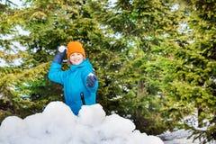 Den lyckliga pojken, i att spela för blåttvinteromslag, kastar snöboll Royaltyfria Bilder