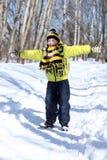 Den lyckliga pojken i en vinter parkerar royaltyfri fotografi