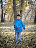 Den lyckliga pojken kastar sidor i höst parkerar arkivbild