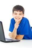 Den lyckliga pojken lär kurser på en bärbar dator Arkivbilder