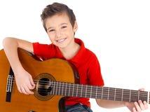 Den lyckliga pojken leker på den akustiska gitarren Arkivfoton