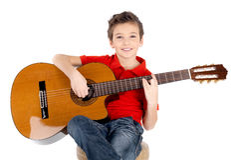 Den lyckliga pojken leker på den akustiska gitarren Royaltyfria Foton