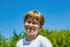 Den lyckliga pojken ler och tycker om liv arkivfoto