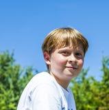 Den lyckliga pojken ler och tycker om liv arkivbilder