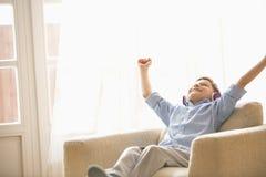 Den lyckliga pojken med armar lyftte att tycka om musik, medan koppla av på fåtöljen hemma Royaltyfri Bild