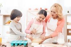 Den lyckliga pojken med bakningmaträtten ser lilla flickan som smäller till deg i bunke med hennes farmor royaltyfri fotografi