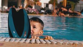 Den lyckliga pojken med flipper simmar i en p?l med bl?tt vatten l?ngsam r?relse lager videofilmer