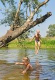 Den lyckliga pojken och flickan leker i laken arkivbild