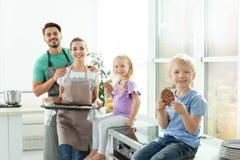 Den lyckliga pojken och hans familjen som äter den hemlagade ugnen, bakade kakor arkivbild