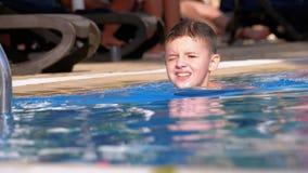 Den lyckliga pojken simmar i en p?l med bl?tt vatten p? hotellet l?ngsam r?relse stock video