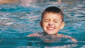 Den lyckliga pojken simmar i en p?l med bl?tt vatten l?ngsam r?relse arkivfilmer