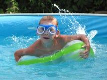 Den lyckliga pojken simmar i pölen. Arkivfoto