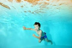Den lyckliga pojken simmar undervattens- i pölen mot bakgrunden av ljusa ljus som ser bort och att le Fotografering för Bildbyråer