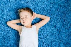 Den lyckliga pojken som ler ungen som ser kameran på blått, mattar i vardagsrum hemma Arkivfoto