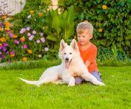 Den lyckliga pojken som omfamnar den vita schweizaren, valler valpen för ` s på grönt gräs arkivfoton