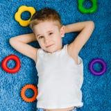 Den lyckliga pojken som ser kameran & ler ungen på blått, mattar i vardagsrum hemma Royaltyfria Foton