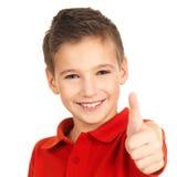 Den lyckliga pojken som visar tum göra en gest upp Arkivfoton