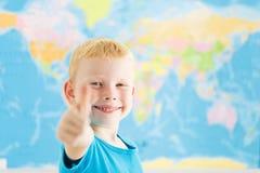 Den lyckliga pojken som visar tum göra en gest upp arkivfoto