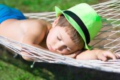 Den lyckliga pojken sover i hängmatta på trädgården Fotografering för Bildbyråer
