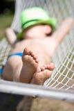 Den lyckliga pojken sover i hängmatta på trädgården Fokusera på fot Arkivfoto