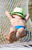 Den lyckliga pojken sover i hängmatta på trädgården Fokusera på fot Royaltyfri Foto