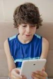 Den lyckliga pojken spelar med notepaden Arkivfoton