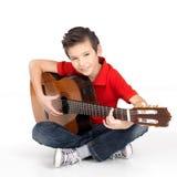 Den lyckliga pojken spelar på den akustiska gitarren Royaltyfri Foto