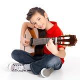 Den lyckliga pojken spelar på den akustiska gitarren Royaltyfri Bild