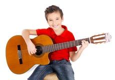 Den lyckliga pojken spelar på den akustiska gitarren Arkivbild