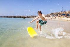 Den lyckliga pojken tycker om att surfa arkivfoton