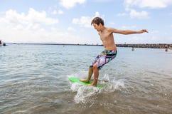 Den lyckliga pojken tycker om att surfa i vågorna Royaltyfri Bild
