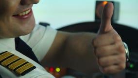 Den lyckliga professionellpiloten i cockpitvisning tummar upp tecknet som tycker om hans arbete arkivfilmer