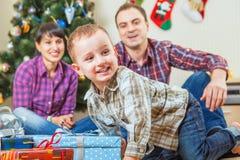 Den lyckliga pysen får en julgåva från jultomten Arkivbilder