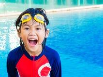 Den lyckliga pysen har gyckel och tycker om i simbassängen arkivbild
