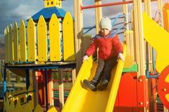 Den lyckliga pysen har roligt och glidning på färgrik modern lekplats in som ska parkeras Royaltyfri Fotografi