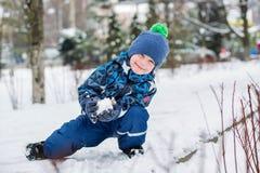 Den lyckliga pysen hugger kastar snöboll royaltyfria bilder