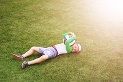 Den lyckliga pysen ligger på fotbollfältet med bollen royaltyfri foto