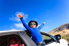 Den lyckliga pysen och flickan reser med bilen in Royaltyfri Fotografi