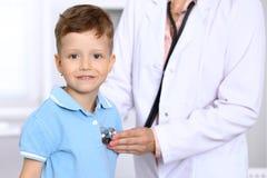 Den lyckliga pysen som har gyckel, medan är, undersöker vid doktorn vid stetoskopet Hälsovård, försäkring och hjälpbegrepp royaltyfri bild