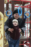 Den lyckliga pysen spelar med modern på lekplatsen i royaltyfri fotografi