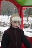 Den lyckliga pysen spelar på lekplatsen i vintern royaltyfria foton