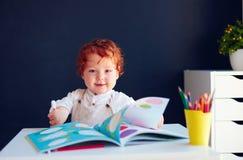 Den lyckliga rödhåriga mannen behandla som ett barn pojketeckningen i framkallande bok på skrivbordet Arkivfoto